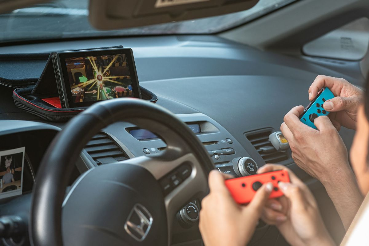 Two people play Nintendo Switch while waiting in drive-thru line at Raising Cane's