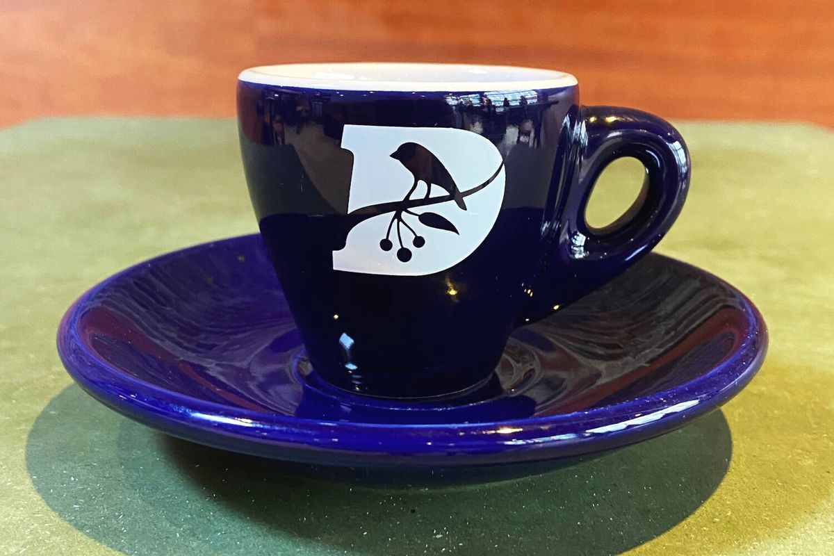 A blue coffee mug with a white logo — which consists of white, upper case D and a silhouette of a bird perched on a branch — sits on a green table cloth, backdropped by a wooden table