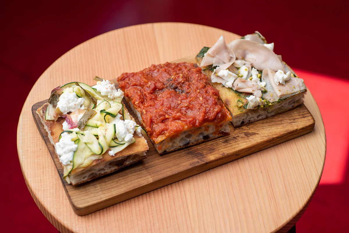 Three squares of flatbread pizza on a wooden table.