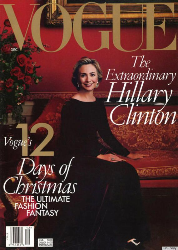 Hillary Clinton sits on a red couch in a velvet dress.