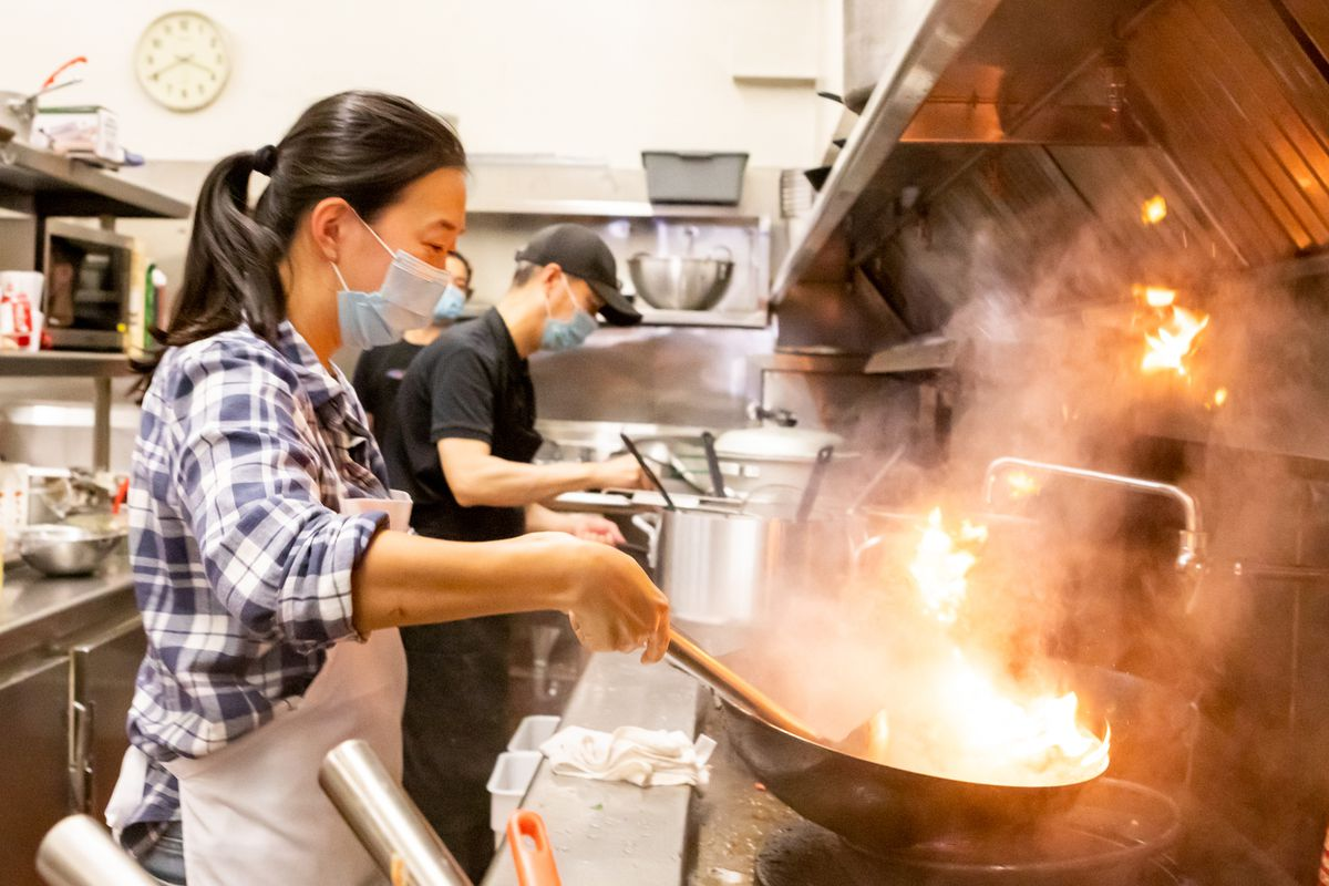 Chef Sandy Zheng cooks something in a hot, flaming wok while wearing a face mask