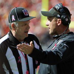 Oakland Raiders head coach Dennis Allen (right) talks to field judge Mike Weir (50) against the Kansas City Chiefs in the second half at Arrowhead Stadium. Kansas City won the game 24-7.