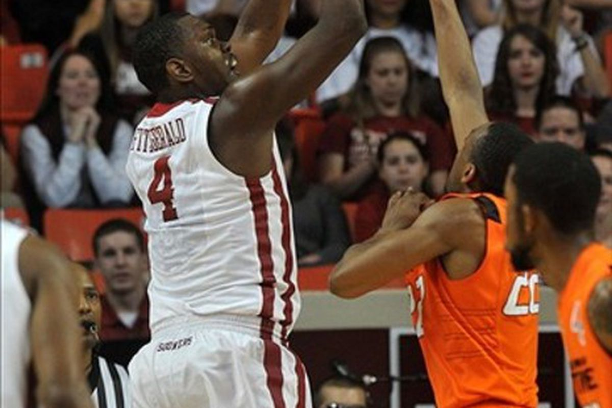 Feb 22, 2012; Norman, OK, USA; Oklahoma Sooners forward Andrew Fitzgerald (4) takes a shot against Oklahoma State Cowboys guard Markel Brown (22) during the first half at the Lloyd Noble Center. Mandatory Credit: Mark D. Smith-US PRESSWIRE