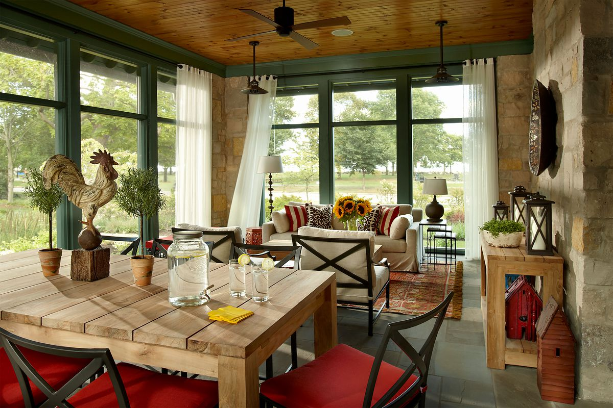 A farmhouse style screened in porch with wood ceilings, green trim and white curtains for privacy.