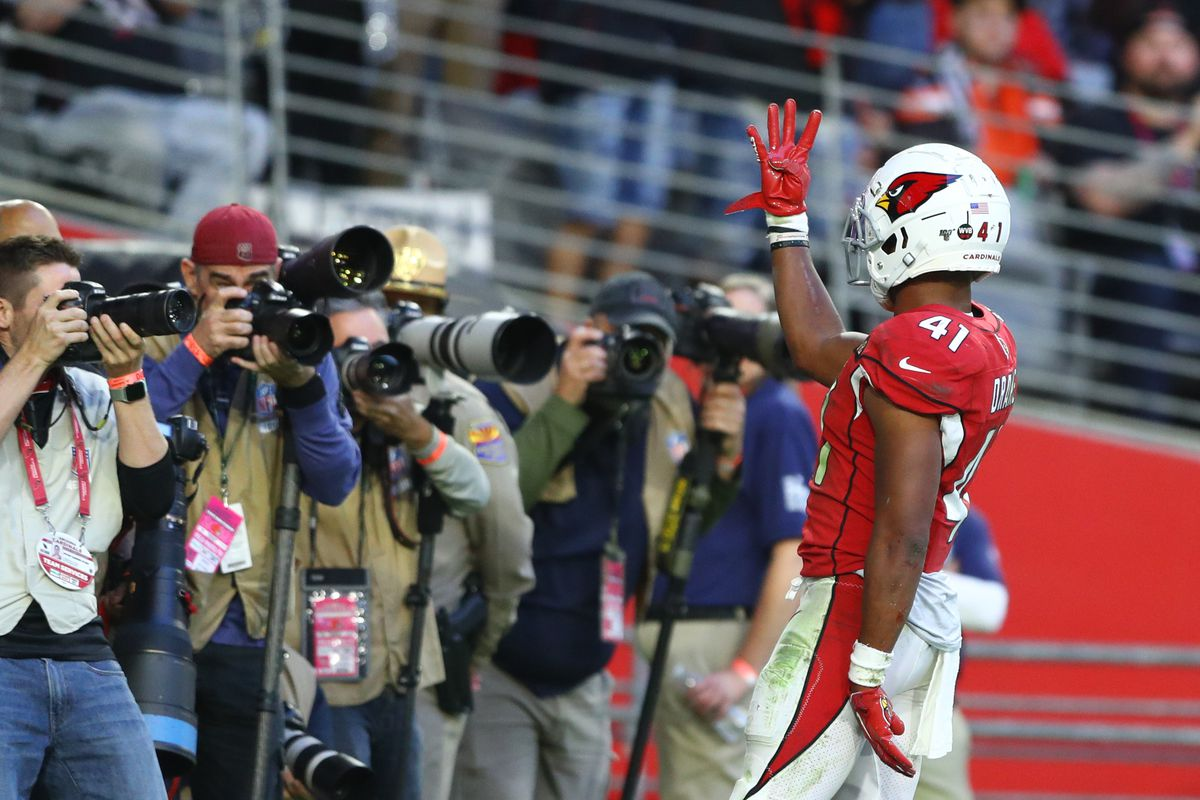 Arizona Cardinals running back Kenyan Drake holds up four fingers celebrates his fourth touchdown of the game in front of sideline photographers in the second half against the Cleveland Browns at State Farm Stadium.