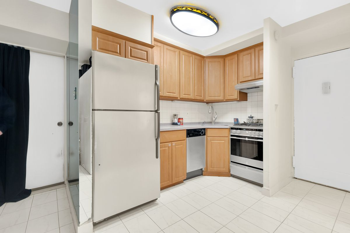 A kitchen with wood cabinetry and tiled floors.