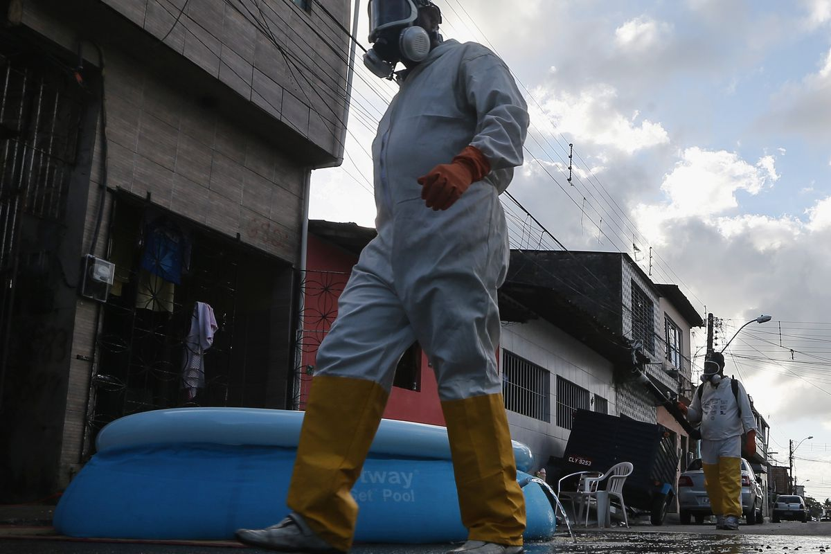 Health workers walk past a draining pool in the street while fumigating in an attempt to eradicate the mosquito which transmits the Zika virus on January 28, 2016, in Recife, Pernambuco state, Brazil.