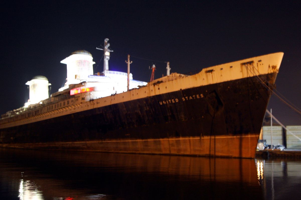 SS United States ship with its smokestacks lit up.