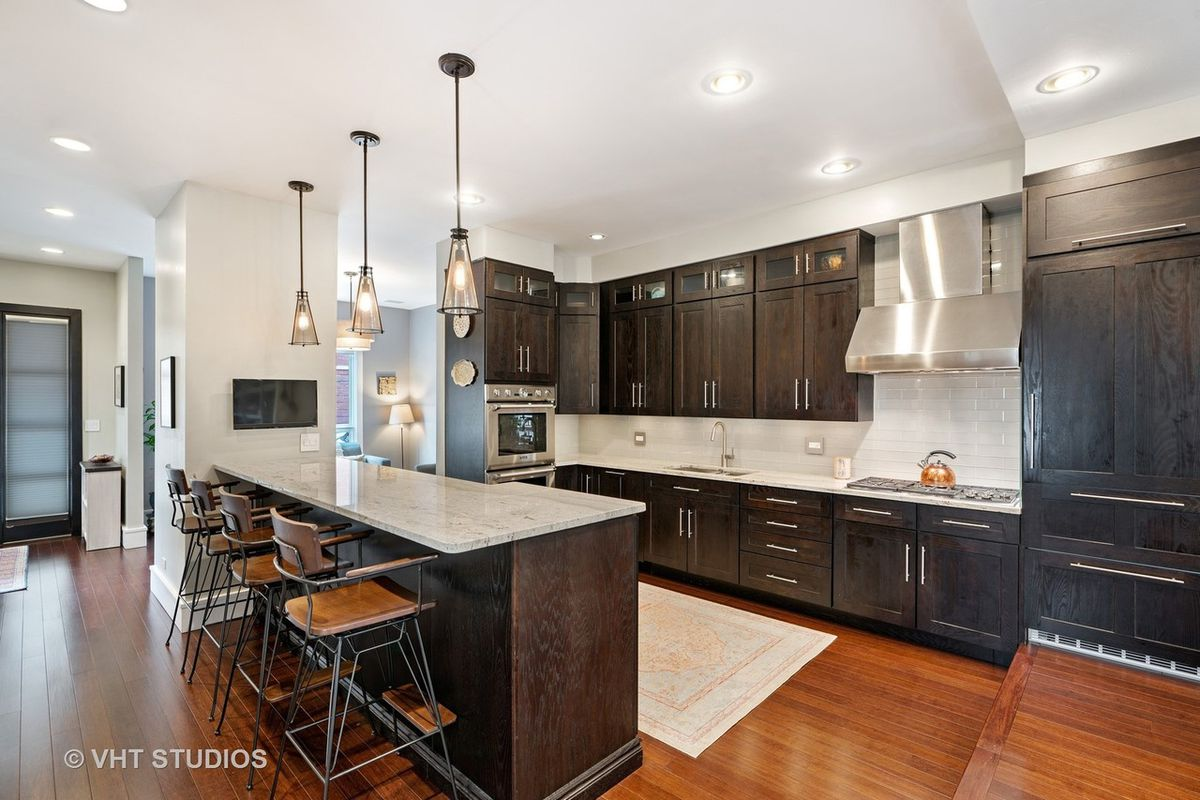 Dark wood cabinets and white marble countertops with four barstools at the island breakfast bar.