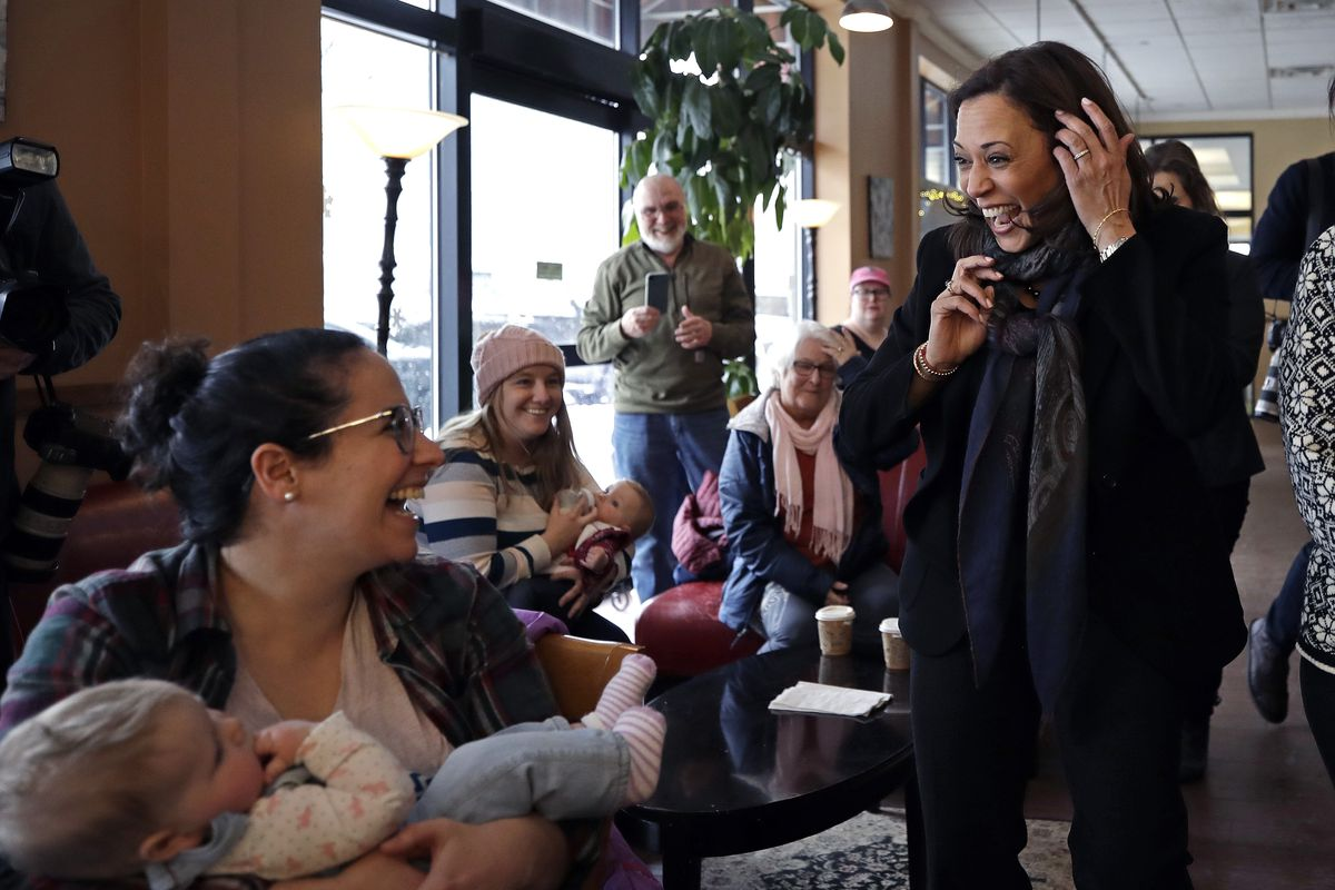 Democratic presidential candidate Senator Kamala Harris walks up to greet a mother cradling a baby at a bookstore.
