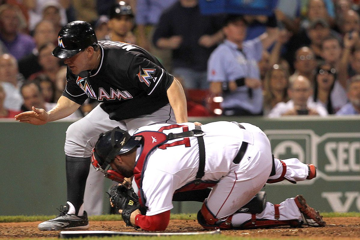 BOSTON, MA - JUNE 19: Kelly Shoppach #10 of the Boston Red Sox tags out Logan Morrison #5 of the Miami Marlins at the plate during interleague play at Fenway Park June 19, 2012  in Boston, Massachusetts.  (Photo by Jim Rogash/Getty Images)