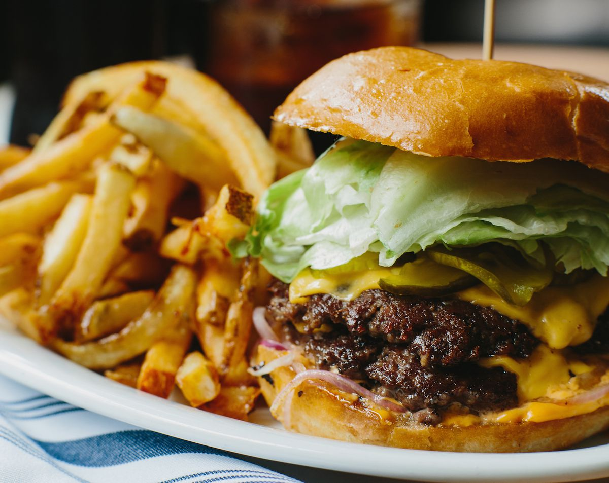 The General Muir cheeseburger topped with lettuce and shaved onions and a plate of fries