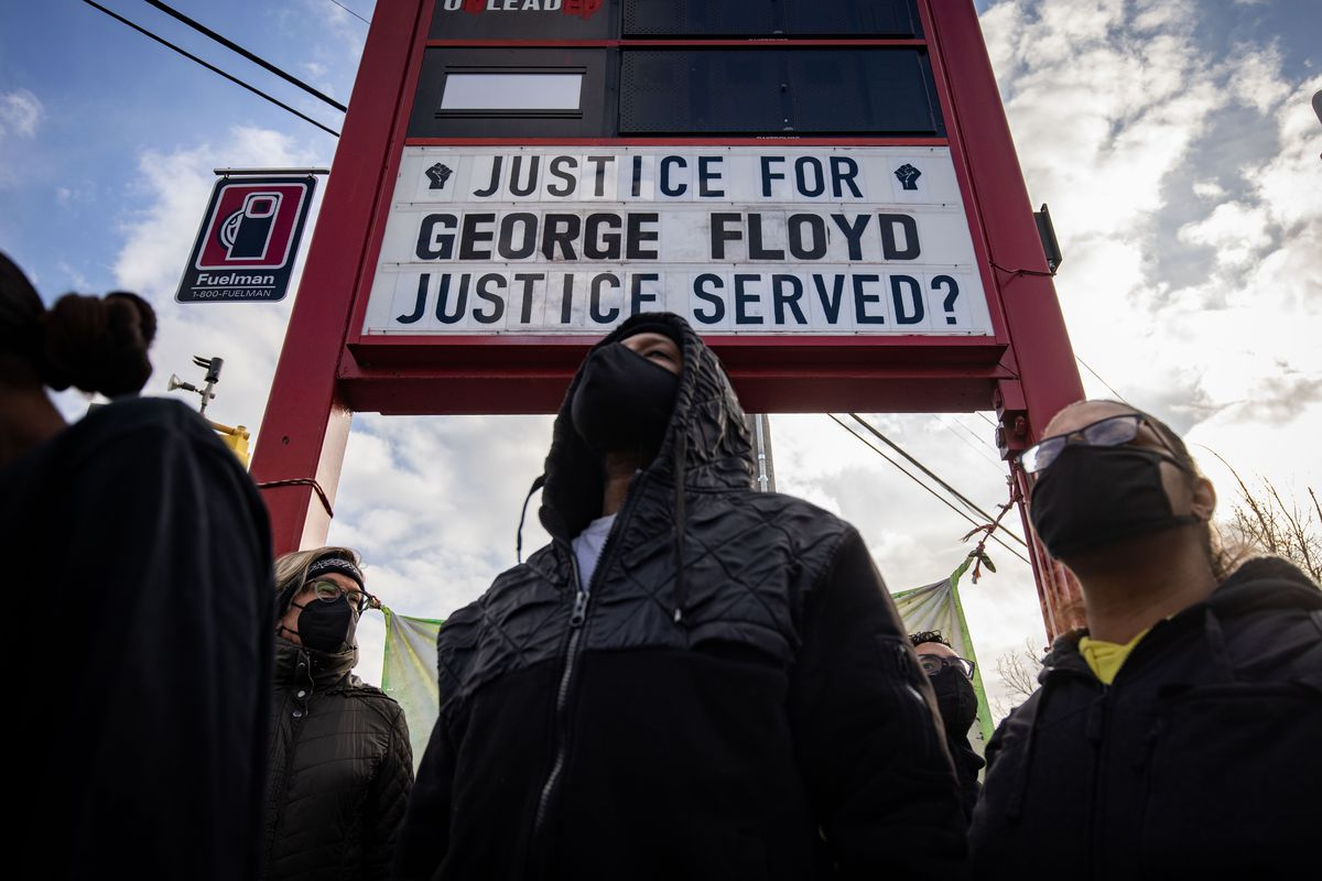 """Black people in masks stand beneath a gas station sign; the area that would normally have the gas prices reads: """"Justice for George Floyd;"""" underneath that is the message: """"Justice served?"""""""