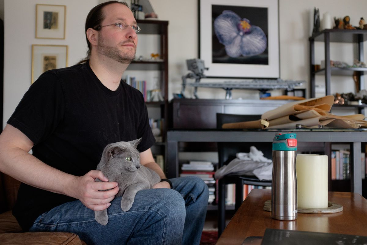 Zucker hanging out in his living room office with the more social of his two cats.