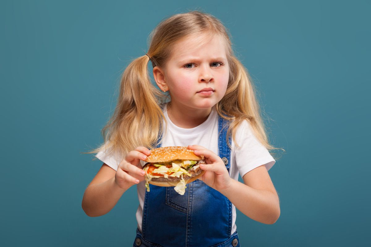A blond girl holds a hamburger, looking confused.