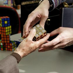 Erno Rubik, left, the inventor of the Rubik's Cube, reaches out to receive a gold and gemstone version of his cube from jeweler Fred Cuellar at Liberty Science Center, Wednesday, April 25, 2012, in Jersey City, N.J. The center will have an exhibit on the toys and will include the diamond version, which is worth 2.5 million dollars.