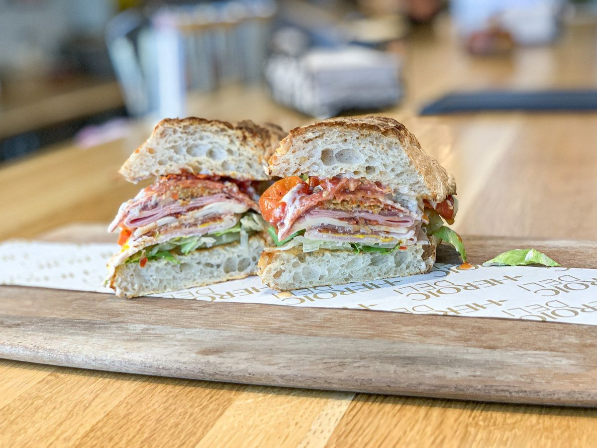A stacked Italian sandwich from a new deli, on a wooden board.