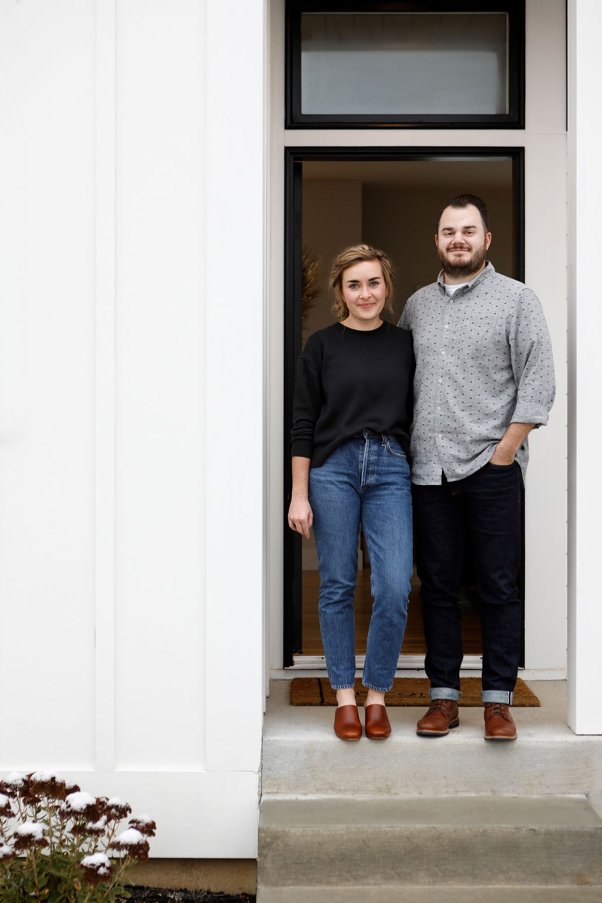 The homeowners, a man and woman, stand outside their front door. The front door is glass and they are both standing at the top of concrete stairs.