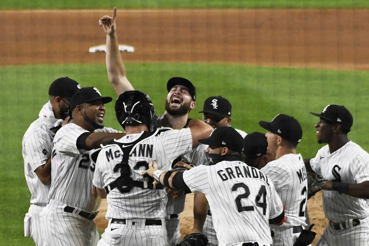 Pittsburgh Pirates v Chicago White Sox - Lucas Giolito raises his right hand in the air to celebrate with his teammates around him on the mound