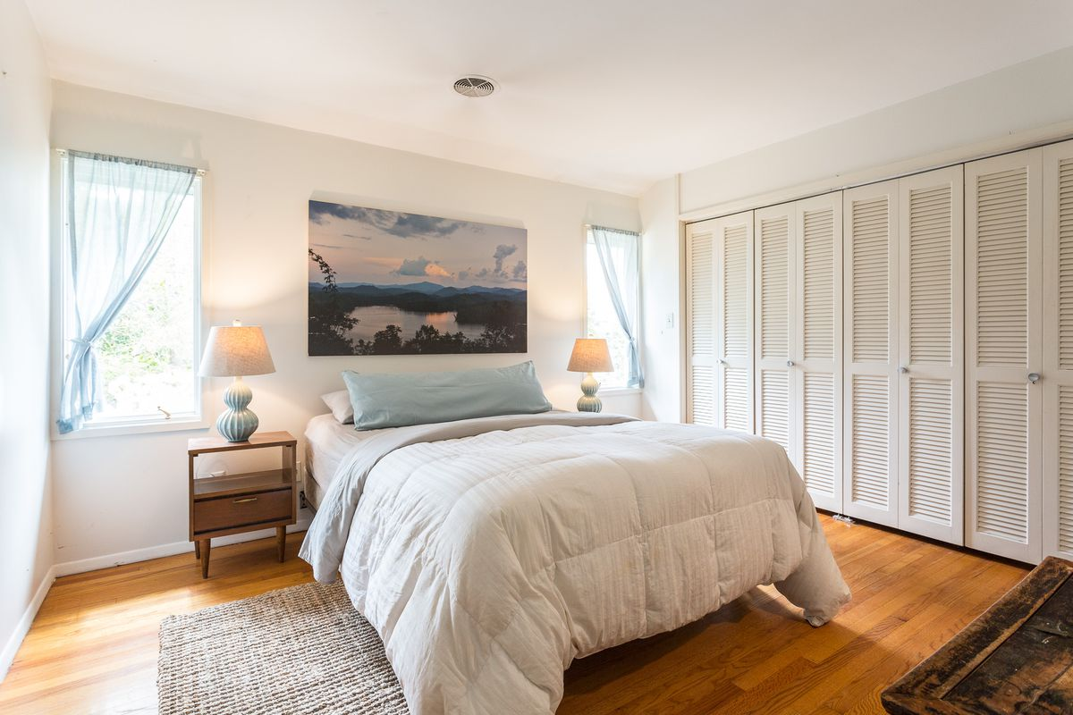 A bedroom has a white bed, two side tables with lamps, and closets on one side.