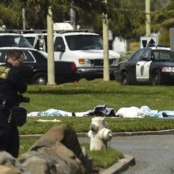 Bodies lie covered on the grass as Oakland Police work near Oikos University in Oakland, Calif., Monday, April 2, 2012. A gunman opened fire at Oikos University in California Monday, killing at least five people, law enforcement sources close to the investigation said. Police say they have a suspect in custody.