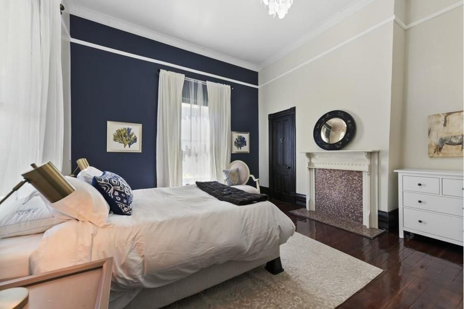 A large blue and white bedroom with a fireplace.