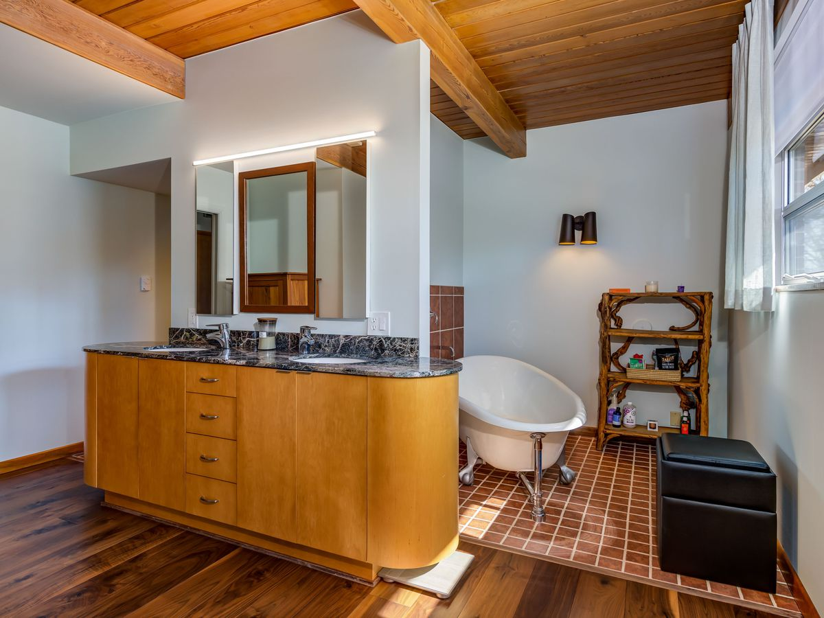 A master bath with a freestanding tub on one side, two sinks, and tile.