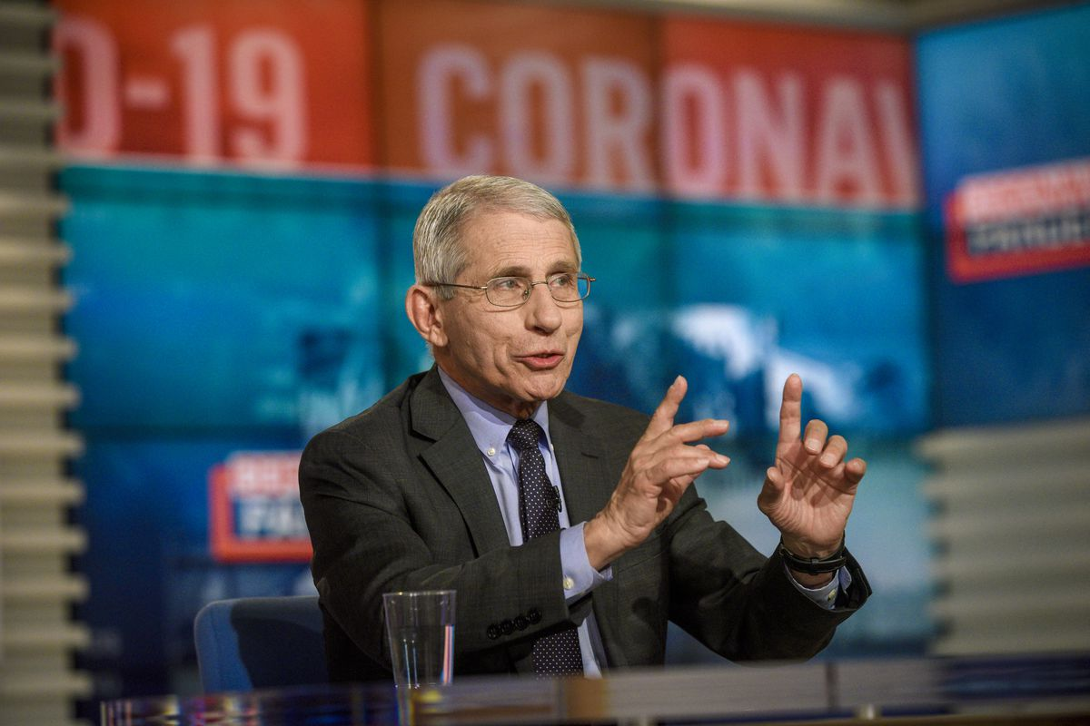 Fauci speaks on the set of Meet the Press, red and blue coronavirus graphics flashing behind him.