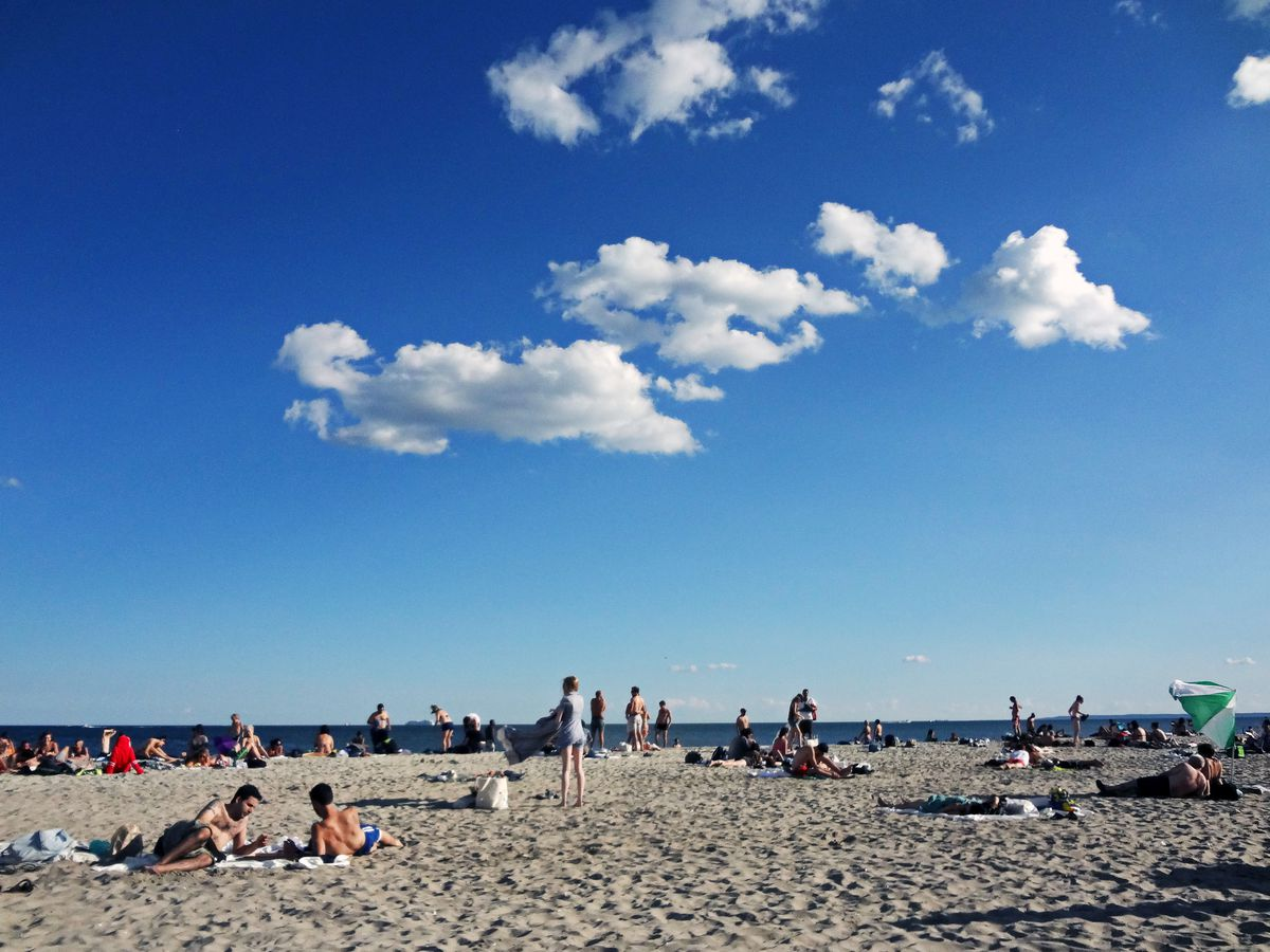 In the foreground is a sandy beach. There are people laying and standing on the sand.
