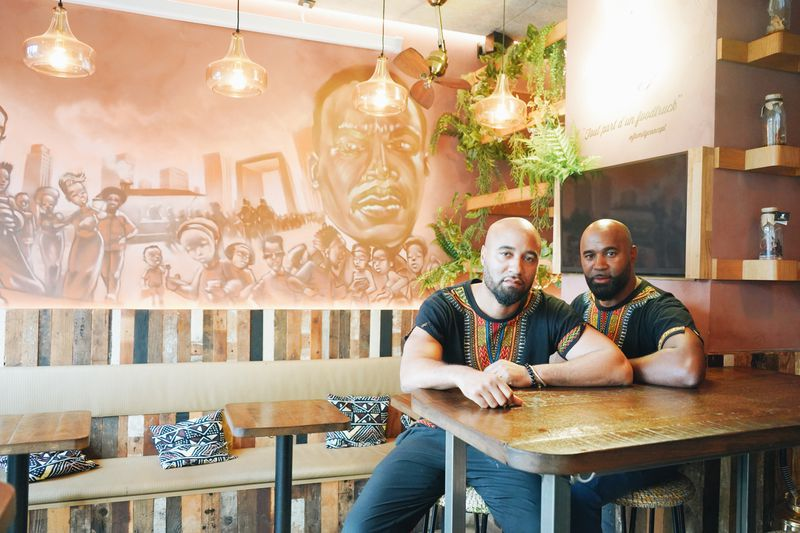 Rude and Joël Lainé sit at a table in New Soul Food-Le Maquis' dining room. Behind them is a large mural, along with small tables that sit in front of banquette lined with pillows.