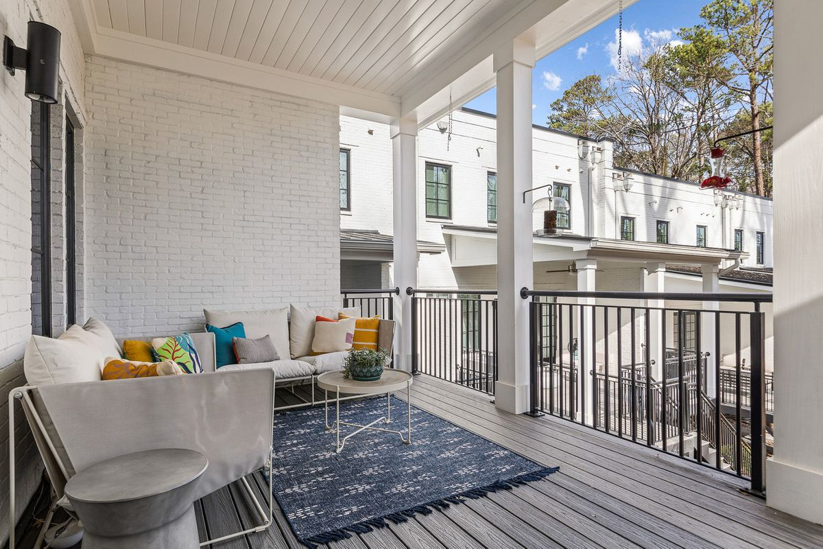 A white patio with cozy furniture on all sides.