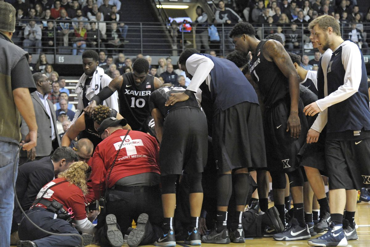 Xavier players huddle around Sumner after first responders stabilized him.