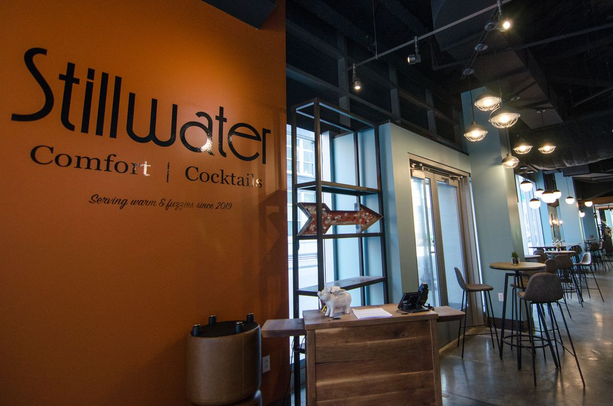 """A wooden host stand at a restaurant. There's an orange wall with text behind it, reading """"Stillwater Comfort Cocktails. Serving warm and fuzzies since 2019."""" In the background, several high-top tables are visible against light blue walls."""