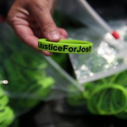 """Linda Rogers shows of a """"Justice for Josh"""" wrist band being sold to raise money at the Capitol in Salt Lake City on Saturday, July 30, 2016. Family members and supporters held a rally to call for the release of Josh Holt, who has been jailed in Venezuela."""