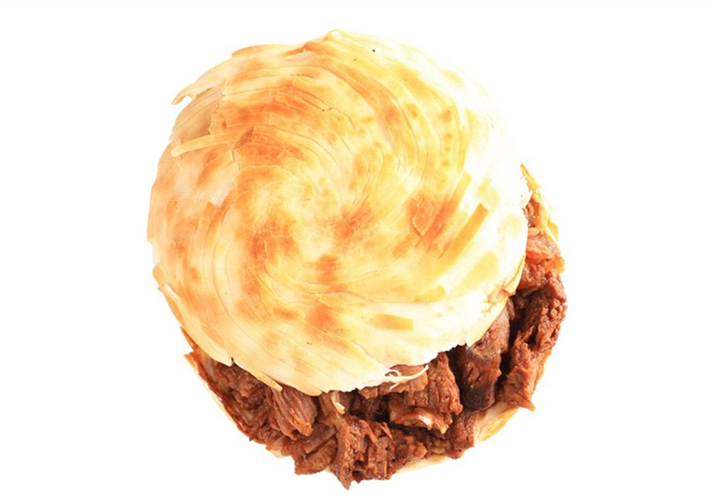 """A rougamo, or Chinese """"burger,"""" sits on a white background, with meat visible between two pieces of flatbread"""