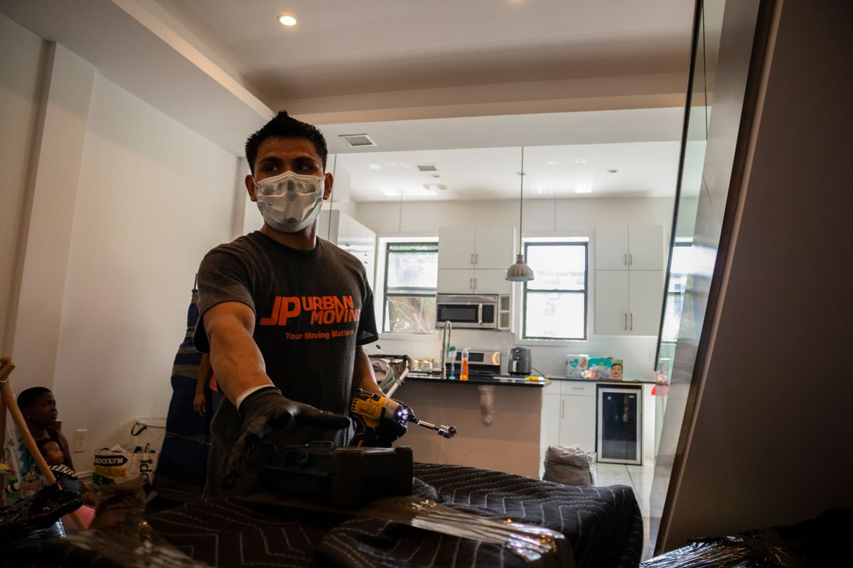 Marcos Rodríguez sweats through his surgical mask after carrying furniture up two flights of stairs, Aug. 14, 2020.