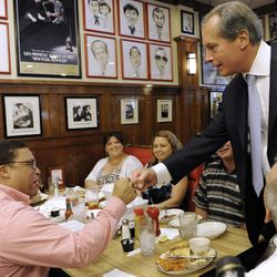 Lt. Gov. David Dewhurst, right, fist bumps Jason Carter at a deli Tuesday, July 31, 2012, in Houston. Dewhurst faces former Texas Solicitor General Ted Cruz in the Republican primary runoff election for U.S. Senator. Carter had jokingly handed Dewhurst his lunch tab and Dewhurst quickly gave it back.