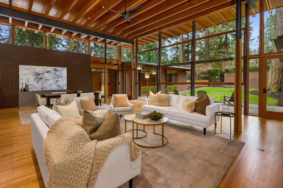 A living room with white couches, tall ceilings, and views of the courtyard.