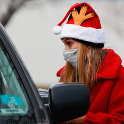 Kariann Atkin checks the registration information of clients during the Big Brother Big Sister's Holiday Drive Thru at a parking lot in Taylorsville on Thursday, Dec. 10, 2020.During the event, Littles (youth living in adversity), their Bigs (Volunteer Mentors) and their families were invited to pick up warm winter coats, gift cards and fun treats.