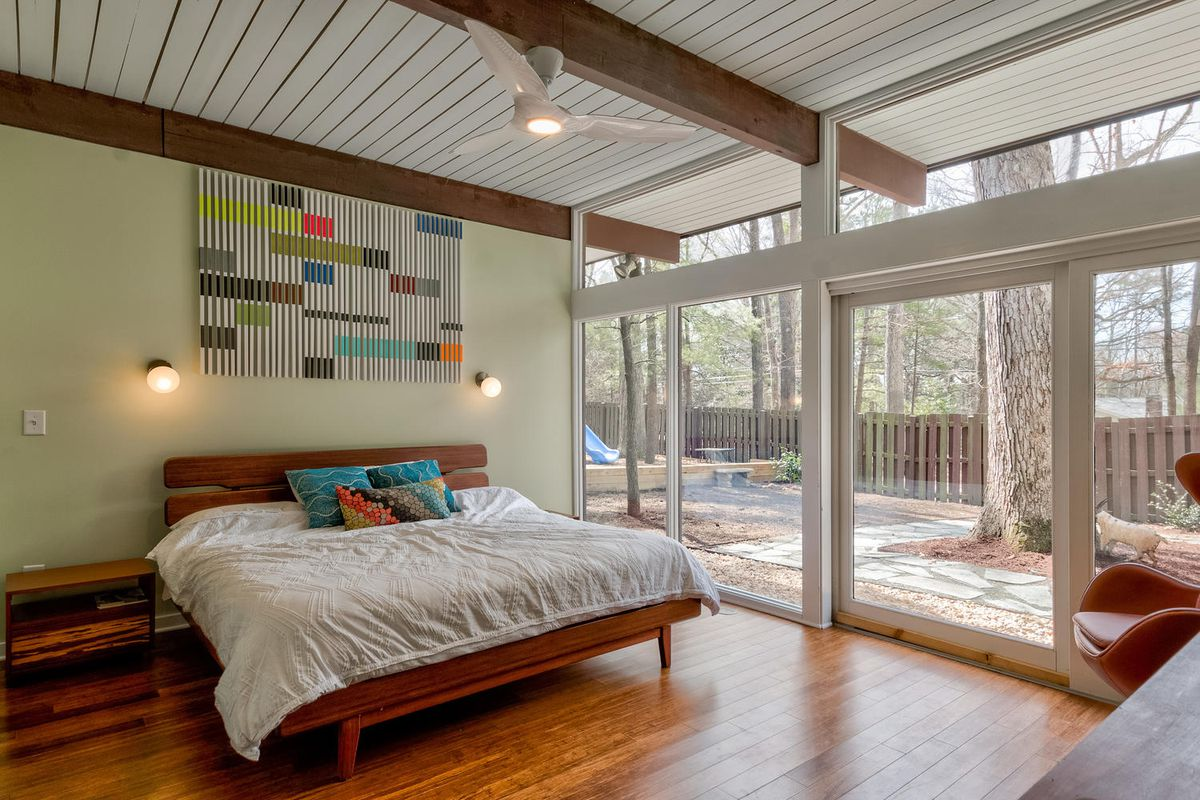 A master bedroom has a large bed, art above it, and one wall of windows that looks out to the yard.
