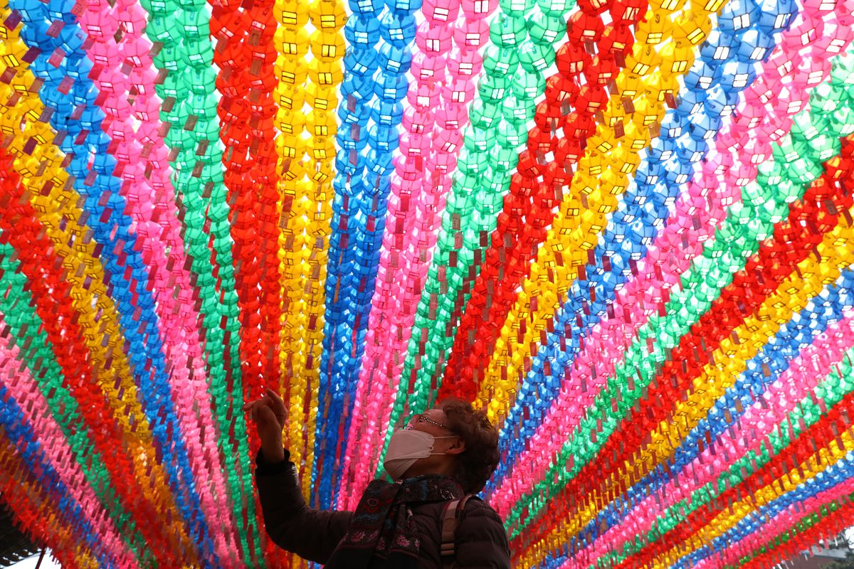 A woman in a mask looks up at dense rows of blue, pink, green, red, and yellow lanterns above her head. The sun streams through them, bathing her in multicolored light.