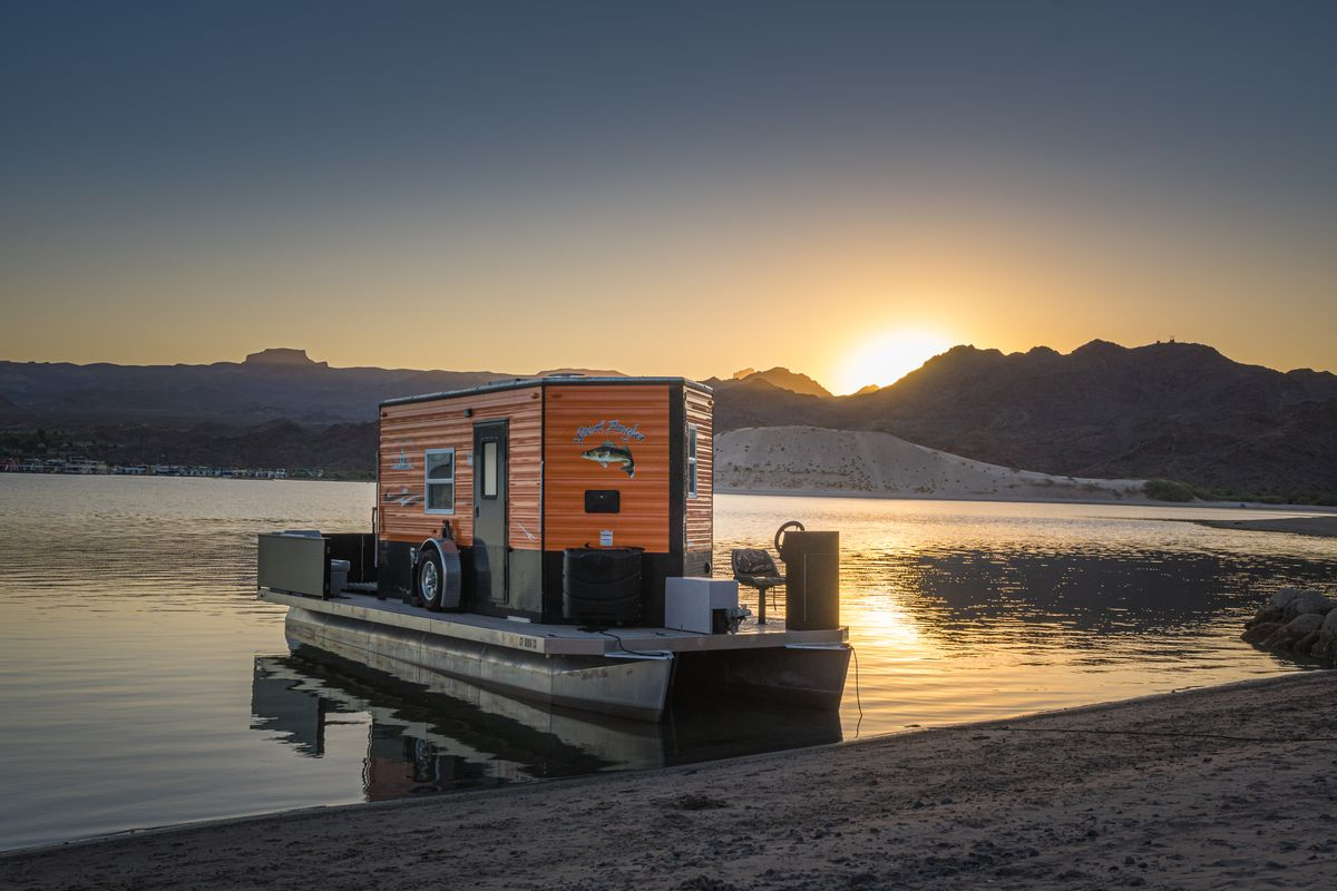 An orange trailer sits on a pontoon-style boat in the water with mountains in the background and the sun setting.