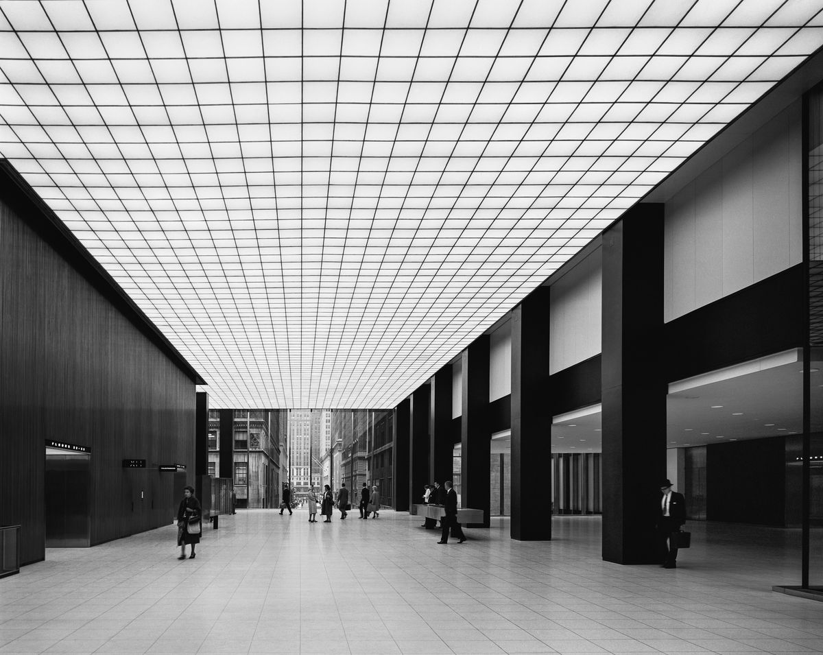 The lobby of a midcentury office building which has an illuminated ceiling with a grid pattern.