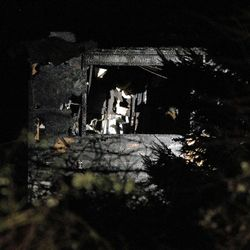 Charred walls can be seen through a gap in the trees at the home of Josh Powell in Puyallup, Washington, Sunday, Feb. 5, 2012.