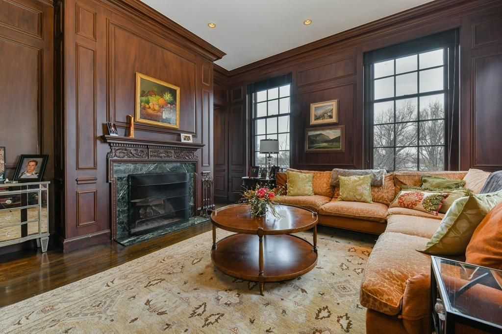 A wood-paneled room with a fireplace and furniture.