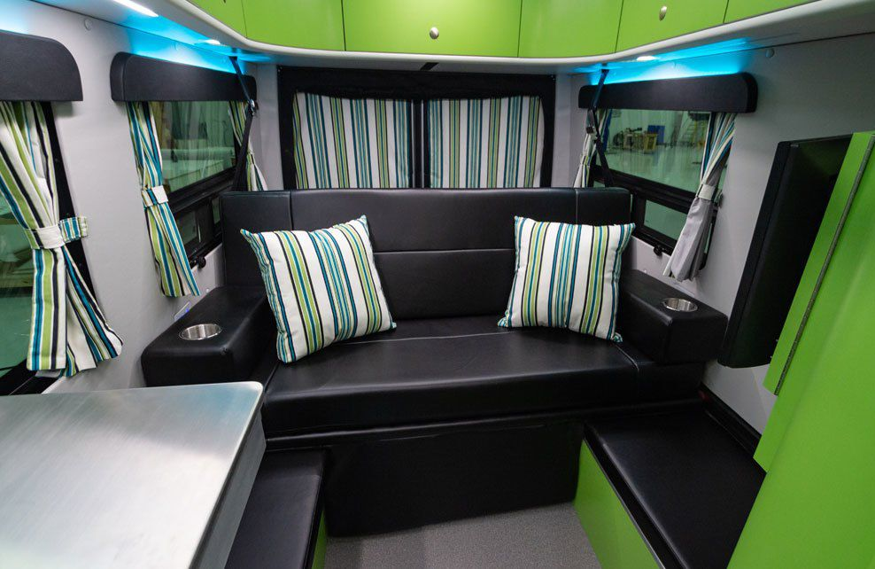 The inside of a Mercedes Sprinter camper van with a black bench seat, striped green and white pillows, and green upper cabinets.