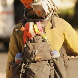 In this Saturday, June 22, 2013 photo released by the Prescott Fire Department, a member of the Granite Mountain Hot Shots carries his equipment while battling the Doce fire near Prescott, Ariz. On Sunday, June 30, 2013, a fast-moving wildfire killed 19 firefighters from the Prescott-based Granite Mountain Hot Shots after the blaze raced through the central Arizona town of Yarnell, about 85 miles northwest of Phoenix. (AP Photo/Prescott Fire Department, Wade Ward)