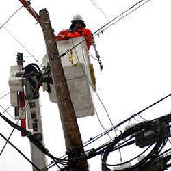 A Utah Power lineman works on lines in the Avenues to restore electricity, lost due to heavy, wet snow.