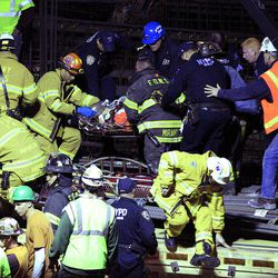 Emergency personal remove an injured man from the site of a crane collapse where construction is going on for the 7 line subway extension Tuesday, April 3, 2012, in New York. Fire officials say a crane collapse at a Manhattan construction site has injured two people.