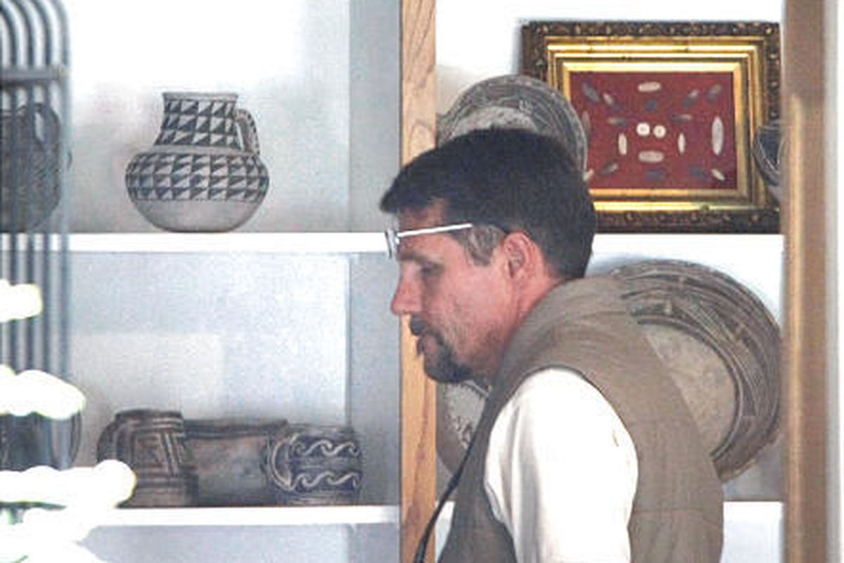 A BLM employee walks past shelves of Native American artifacts at Vern Crites' home in Durango on Wednesday.